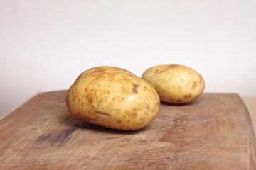 Two potatoes on chopping board
