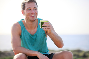 Green smoothie man drinking vegetable juice