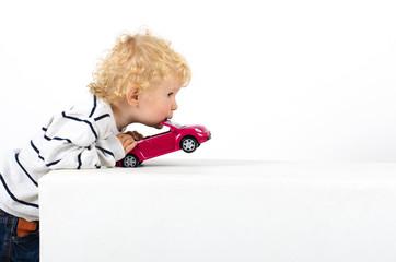 Kleinkind spielt mit Modelauto