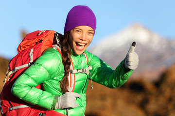 Hiking woman in winter jacket giving thumbs up
