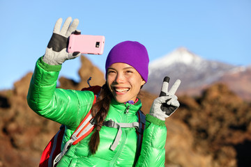 Woman hiker taking selfie photo hiking in winter