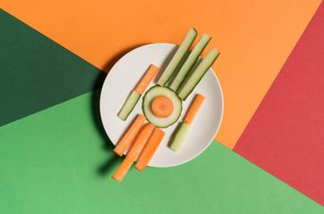 Teller mit Gemüsesticks auf Untergrund aus geometrischen Formen