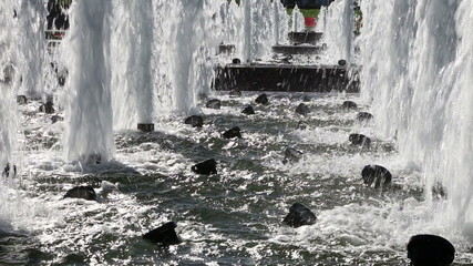 Water pours from a large fountain. Closeup