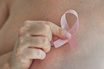 woman hand holding pink ribbon, a breast cancer symbol