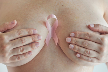 Pink ribbon, a breast cancer symbol, over woman chest