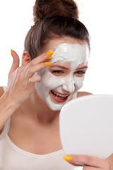 young woman enjoys applying face mask