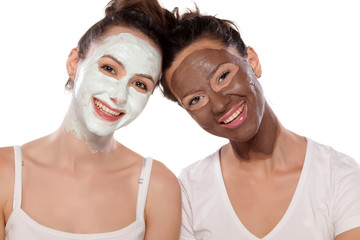 two smiling young women with masks posing on white