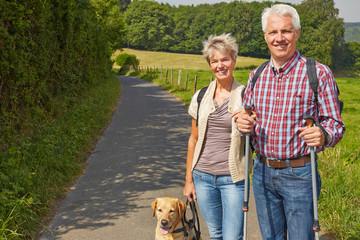 Senioren wandern mit Hund im Sommer