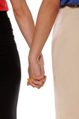 Two women standing and holding each other's hand