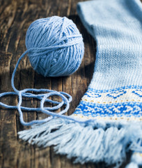 Ball of yarn and knitted scarf on wooden background