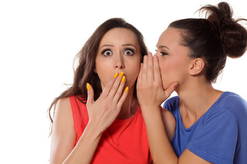 young woman whispers to her mate shocking news