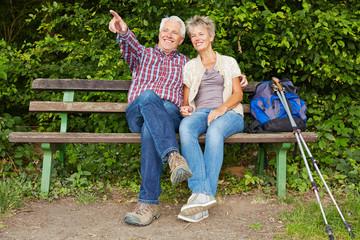 Paar Senioren sitzt auf Bank bei Wanderung