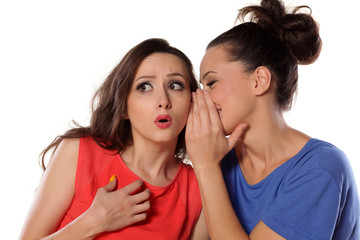young woman whispers to her mate bad news