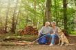 Paar Senioren sitzt mit Hund im Wald