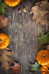 Autumn leaves and pumpkins on the wooden background