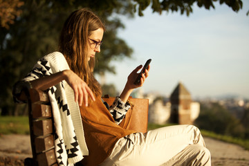 Fashion Young Girl Using Smart Phone On Bench In Park