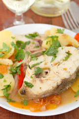 fish stew on white plate with white wine