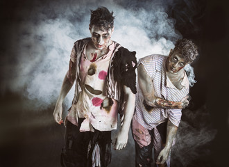 Two male zombies standing on black smoky background