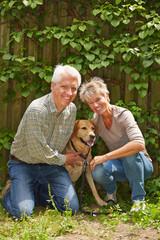 Zwei Senioren mit Hund im Garten