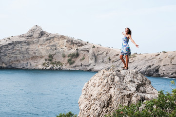 Young woman with backpack standing on cliff's edge
