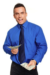Surprised young businessman in blue shirt with money in hand