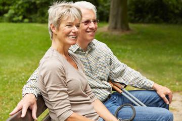 Paar Senioren sitzt auf Bank im Sommer