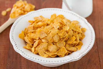 corn flake in white dish on brown background