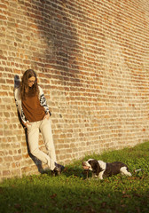 Girl And Dog Chewing Stick At Brick Wall Outside