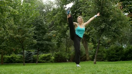 Young beautiful woman doing stretching exercise outdoors