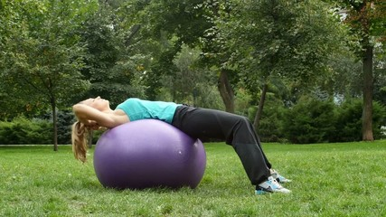 Athletic young sports woman using exercise ball