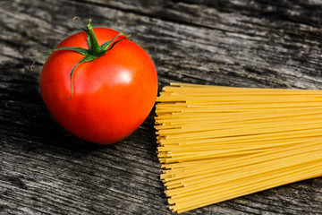 Spaghetti and tomato on a rustic wooden bench