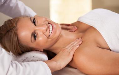 Smiling woman having shoulder massage