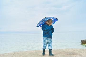 Outdoor portrait of a cute toddler boy under umbrella