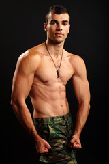 Muscular young military man poses on dark background