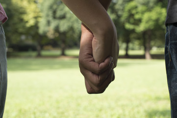 The hands of men and women holding hands in the park