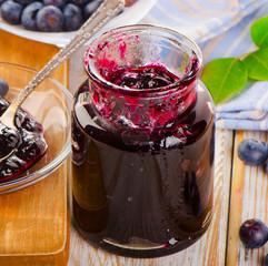Fresh blueberries jam  in a glass jar.