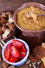 Fondue, slices of cheese, tomatoes and biscuits