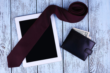Tablet, wallet with money and tie on wooden background