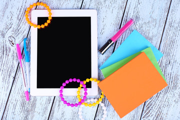 Tablet, bracelet, notebook and pen on wooden background