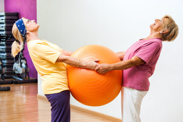 Elderly women stretching with gym ball.