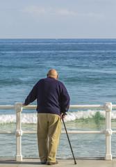 Anciano con bastón mirando al mar