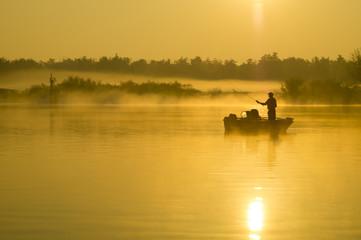 wędkarz na łodzi łowiący ryby w rzece pośród mgieł