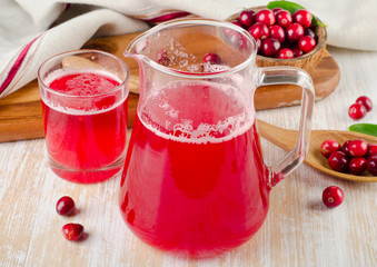 Cranberry drink with fresh berries on  wooden background