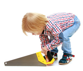 Little boy sawing saw.