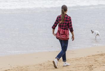 Chica jugando con perro en la playa