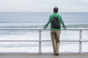 Hombre con mochila frente al mar