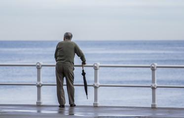 Anciano con paraguas frente al mar