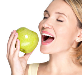 Beautiful young woman biting the biting a fresh ripe apple