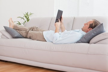 Casual man using tablet on the couch