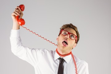 Geeky businessman strangling himself with telephone